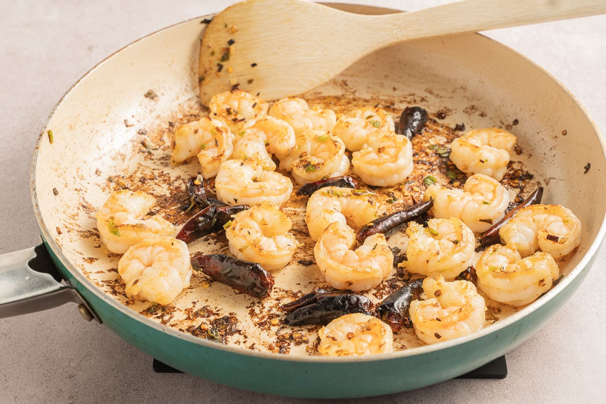 shrimp, chili peppers in fry pan with wooden spoon