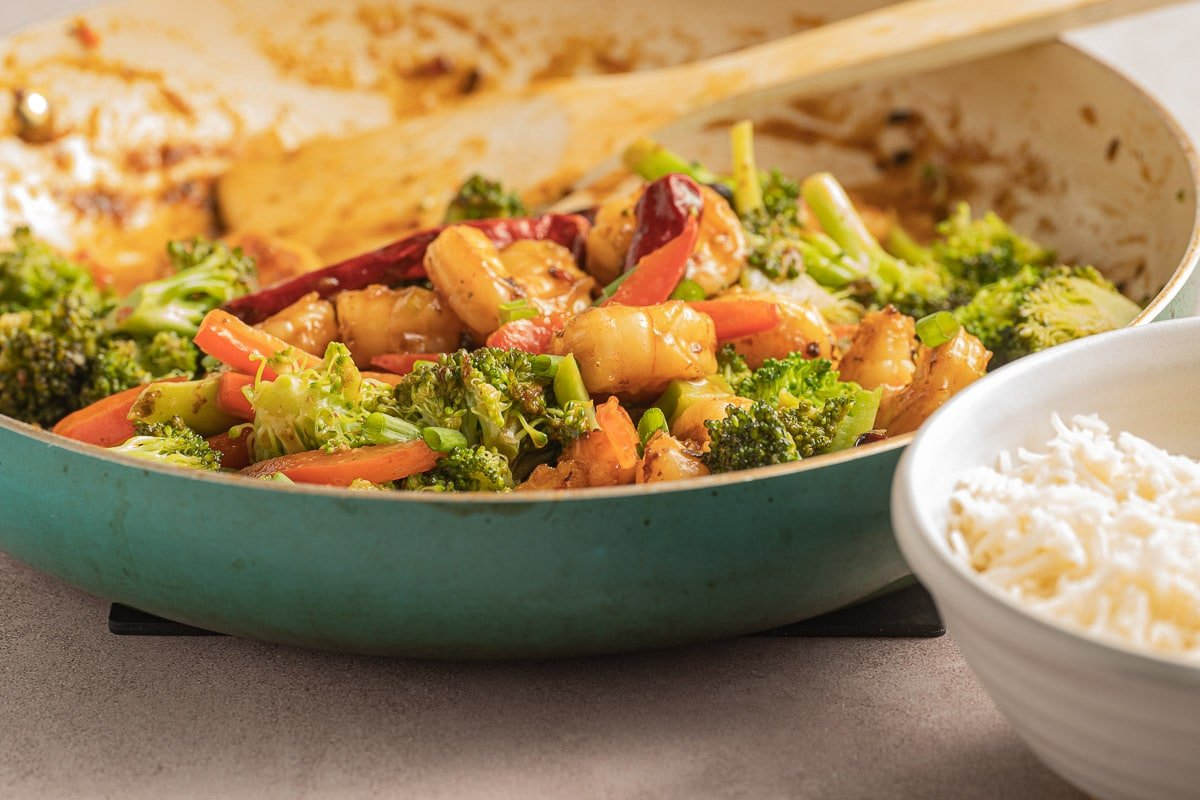 sauteed shrimp, broccoli, red peppers, sauce in fry pan with wooden spoon.