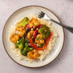 shrimp, broccoli, red pepper over cauliflower rice on beige plate with fork