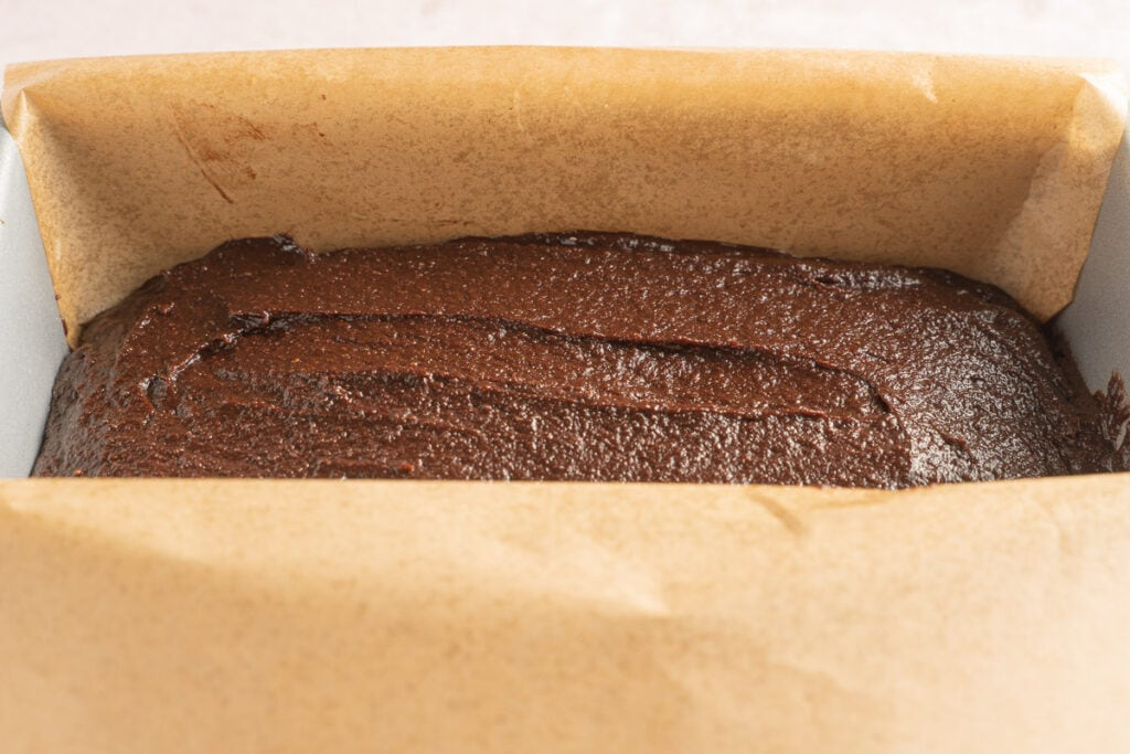 chocolate pumpkin batter in parchment lined loaf pan.