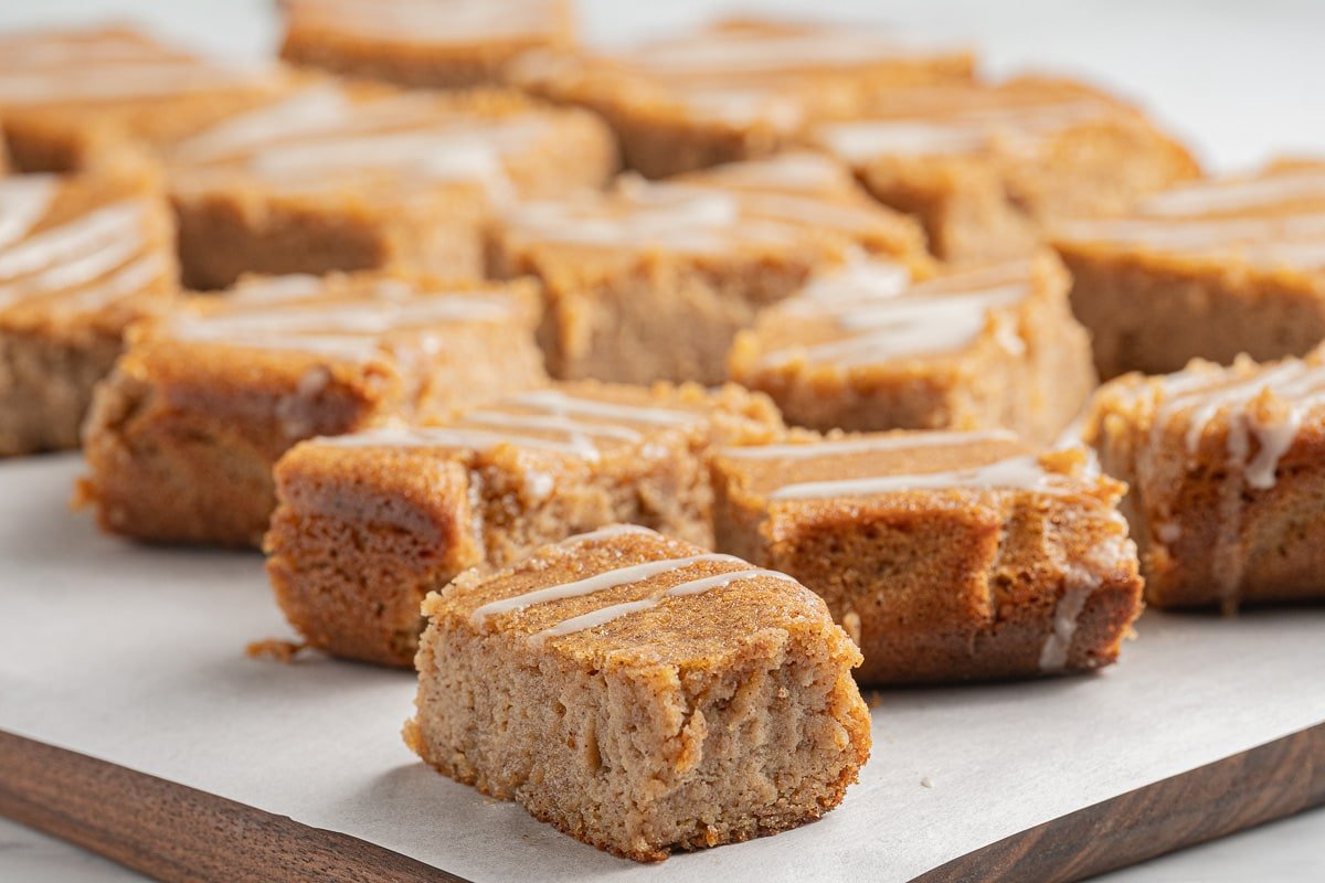 squares of keto spice cake with glaze on cutting board