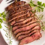 sliced flank steak on white platter with herbs