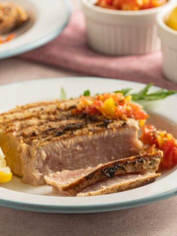 tuna steaks on white plate with lemon slices and tomato relish.