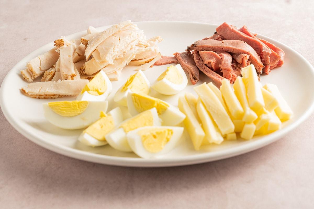 sliced turkey, roast beef, cheese, hard boiled eggs on white plate.