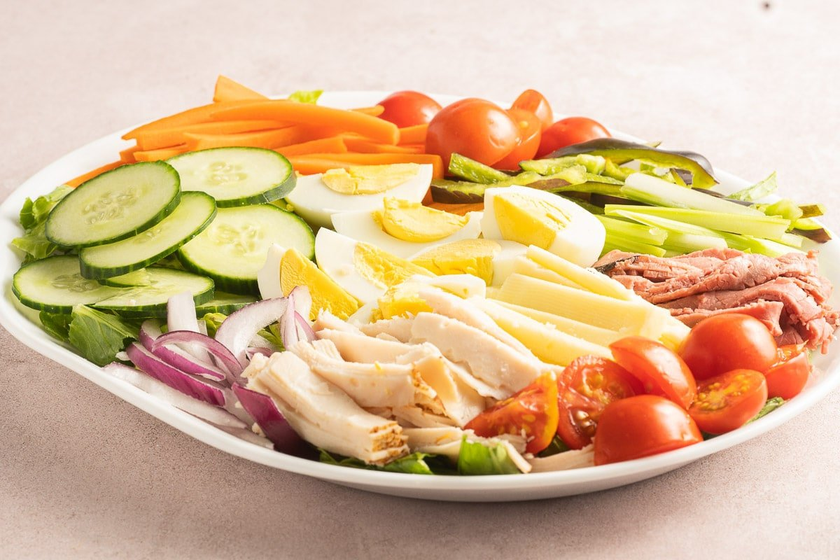 salad with sliced turkey, roast beef, cheese, peppers, cucumbers, tomatoes, radishes, onions, carrots on white platter.