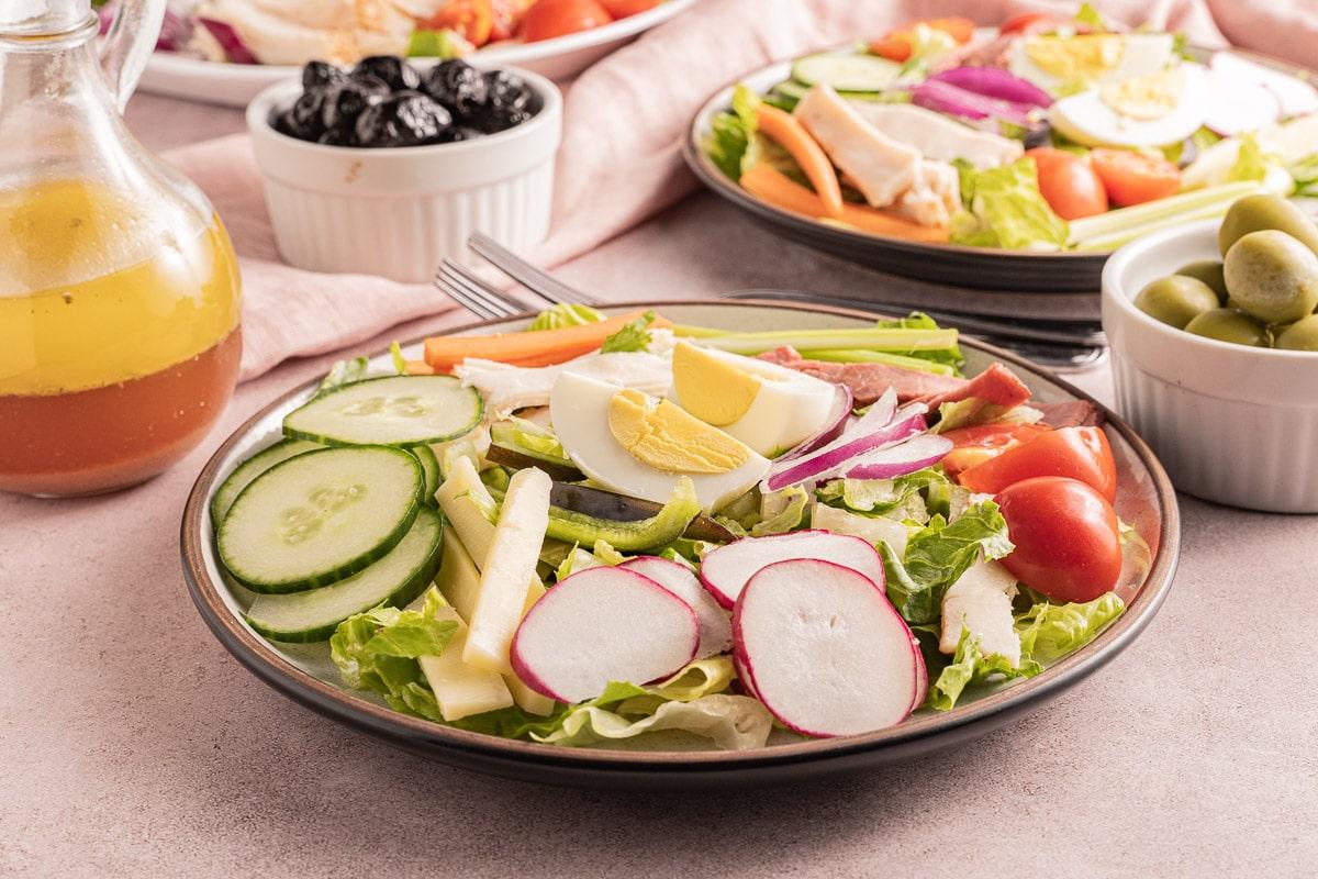 plates of salad sliced turkey, ham, hardboiled eggs, cucumber, radishes, tomatoes, olives in white bowl, cruet of dressing.